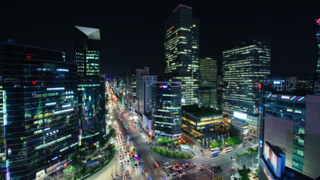 ws t/l pan view of traffic moving near gangnam station intersection with sky scrappers at night / seoul, south korea - seoul stock videos & royalty-free footage