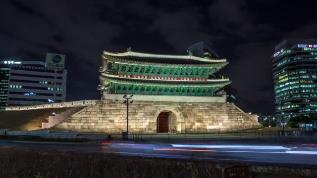 ws t/l zi view of traffic moving near sungnyemun gate / seoul, south korea - 乗り物の明かり点の映像素材/bロール
