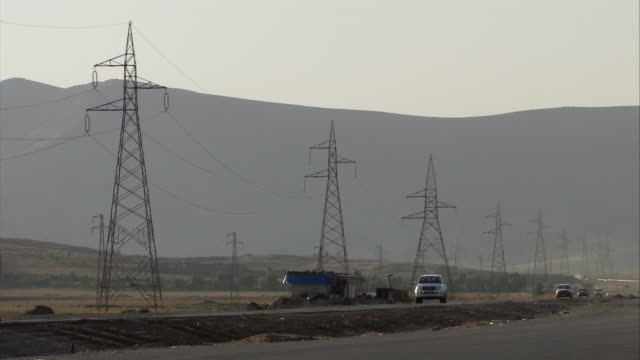 ws view of traffic moving on highway in front of hills and telephone poles / sulaymaniyah, kurdistan, iraq - power line stock-videos und b-roll-filmmaterial