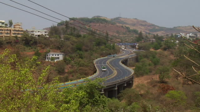 ws view of traffic moving on highway, mountain in background / mumbai, maharashtra, india - main road stock videos & royalty-free footage
