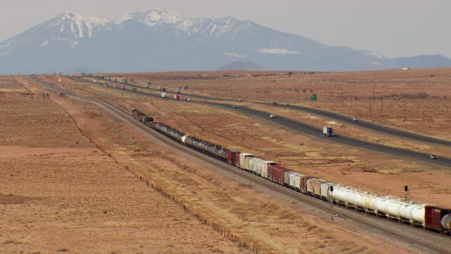 ws aerial view of traffic moving on highway with train passing parallel to highway through desert / arizona, united states - freight train stock videos & royalty-free footage
