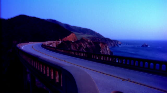 T/L WS View of traffic on Bixby bridge, mountain in background / Big Sur, California, USA