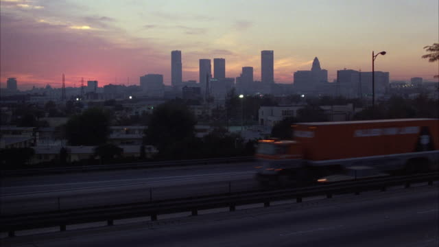 WS View of traffic on freeway with Los Angeles downtown skyline in background / Los Angeles, California, USA