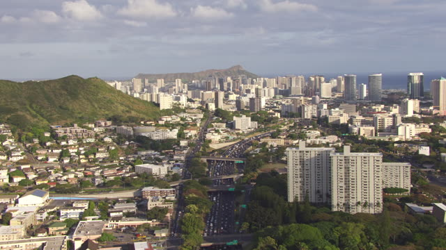 WS AERIAL View of traffic on highway with Honolulu skyline and Diamond Head in background / Hawaii, United States