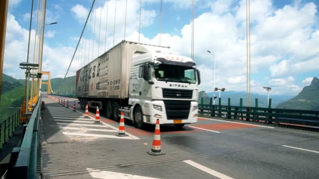stockvideo's en b-roll-footage met uitzicht op het verkeer op siduhe suspension bridge, hubei, china. - vrachtwagentransport