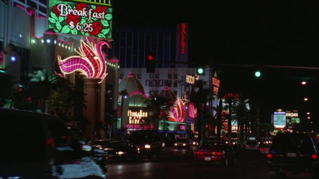 ws view of traffic on street along lass vegas strip with hilton hotel in background / las vegas, nevada, usa - flamingo hilton stock videos & royalty-free footage