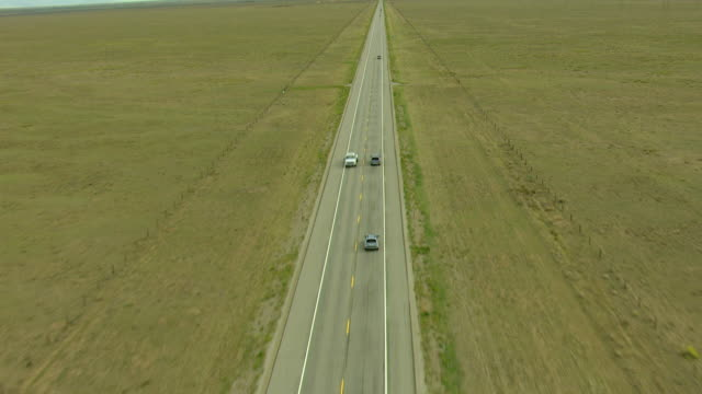 MS TU ZI AERIAL View of traffic traveling on freeway running through flat plains in villa grove saguache county / Colorado, United States