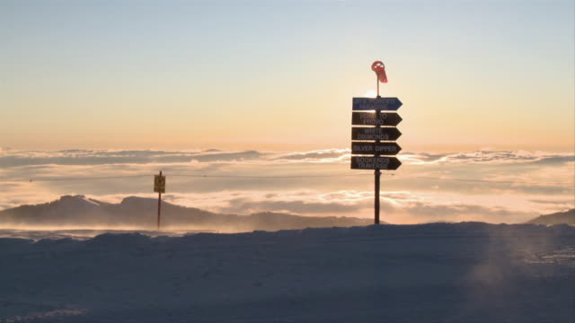 ws view of trail marker signs on snow covered peak at sunrise / alta, snowbird, utah, usa - ユタ州 アルタ点の映像素材/bロール