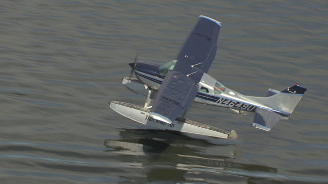 MS AERIAL TS View of Trail Ridge Air airplane taking off at Lake Hood Seaplane Base to airport building / Anchorage, Alaska, United States