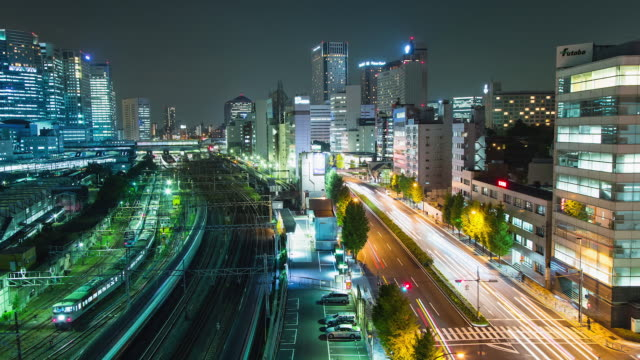 ws t/l view of train and car traffic at shinagawa station at night / tokyo, japan - compartment stock videos & royalty-free footage