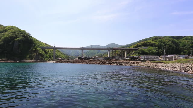 ws view of train crossing amarube viaduct railway bridge and fishing village / mikata district, kami, hyogo prefecture, japan  - fishing village stock videos and b-roll footage
