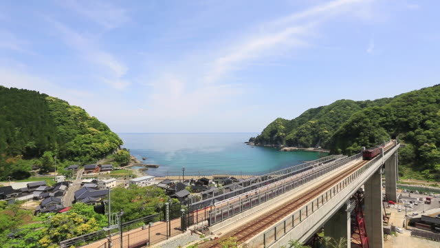 ws view of train crossing amarube viaduct railway bridge / mikata district, kami, hyogo prefecture, japan  - ponte video stock e b–roll