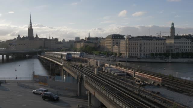view of train lines and trains with gamla stan skyline visible from slussen, stockholm, sweden, scandinavia, europe - stockholm bildbanksvideor och videomaterial från bakom kulisserna