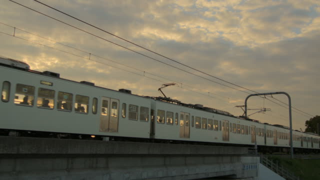 ws view of train passing at sunset / kawagoe, tokyo, japan - ケーブル線点の映像素材/bロール