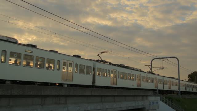 ws view of train passing at sunset / kawagoe, tokyo, japan - cable点の映像素材/bロール