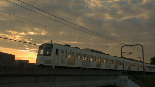 WS View of Train passing at sunset / Kawagoe, Tokyo, Japan