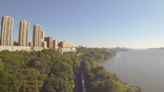 WS AERIAL SLO MO TD View of train running on tracks and sky scrappers with Hudson river / New York, United States