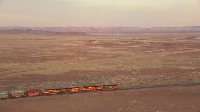 ws aerial ts view of train traveling on tracks with mountains in cibola county / new mexico, united states - new mexico stock videos & royalty-free footage