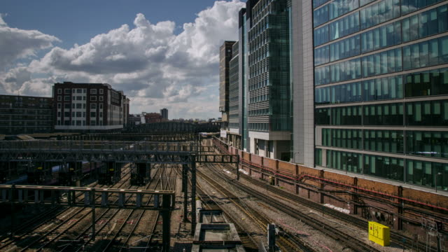 WS T/L View of trains arriving and departing Paddington Station London with clouds reflecting in new office development windows / London, Greater London, United Kingdom