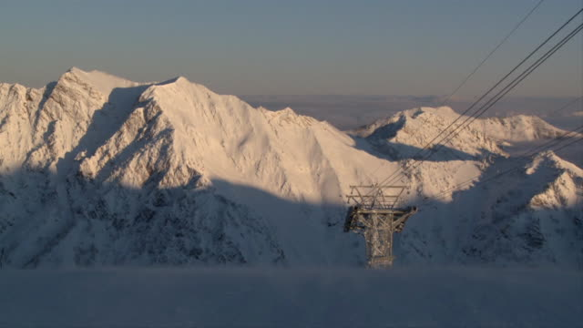ws view of tram tower, snow covered mountains in background at sunrise / alta, snowbird, utah, usa - ユタ州 アルタ点の映像素材/bロール