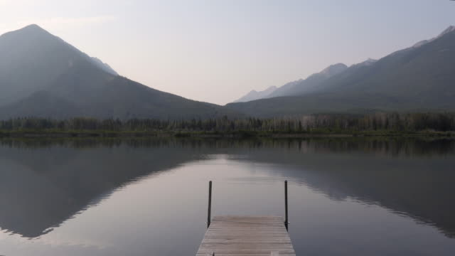 view of tranquil lake and distant mountains - pier stock videos & royalty-free footage