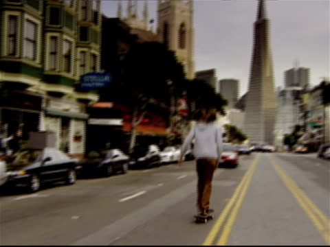 view of transamerica pyramid at end of columbus avenue / boy skateboarding down middle of street past traffic / san francisco, california - 2002 stock videos & royalty-free footage