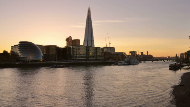 ws t/l view of transition from day to night view across river thames to southbank of central london with city hall shard and hms belfast in view with river traffic passing / london, greater london, united kingdom - shard london bridge stock videos & royalty-free footage