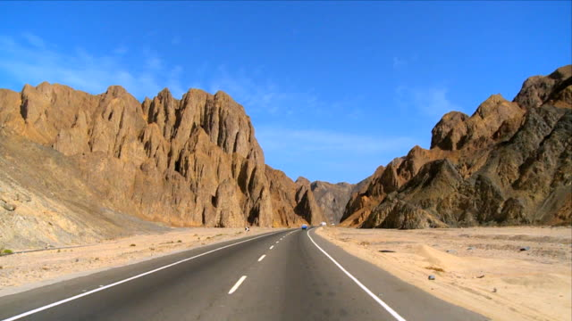 ws pov view of transports moving on road to hurghada near mountains / eastern desert, egypt - winding road stock videos & royalty-free footage