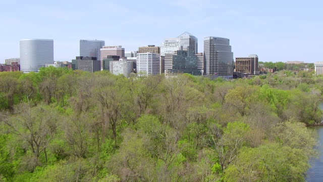 vídeos de stock, filmes e b-roll de ws aerial pov view of trees along potomac river approaching downtown buildings / rosslyn, arlington county, virginia, united states  - arlington virgínia