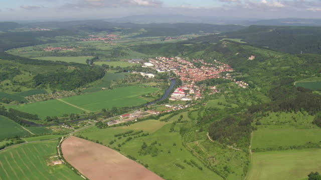 ws aerial view of treffurt and houses with werra river near national park heinich / germany - turingia video stock e b–roll
