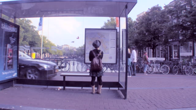 ws view of trolley stop in amsterdam / amsterdam, netherlands - bushaltestelle stock-videos und b-roll-filmmaterial