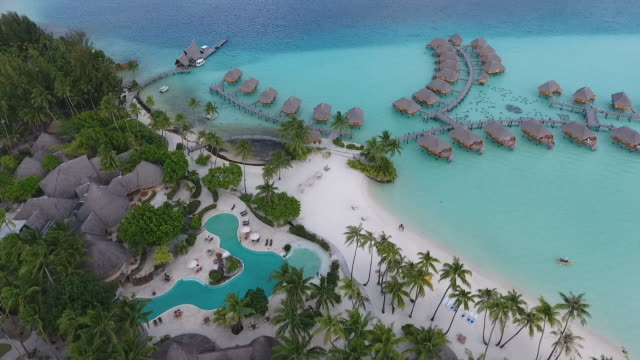 stockvideo's en b-roll-footage met aerial view of tropical forest and bungalows - frans polynesië