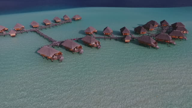 AERIAL view of tropical lagoon and overwater bungalows
