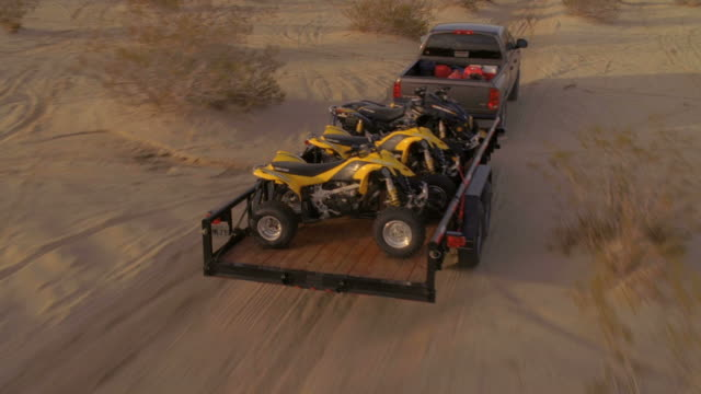 ws pov view of truck pulling trailer with motor bikes on it  through desert  / cougar buttes, california, usa - trailer stock videos & royalty-free footage