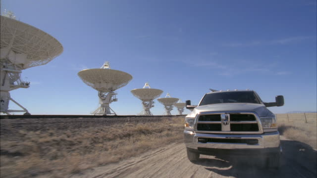 ws pov view of truck with trailer driving in very large array in arid desert  / san augustine, new mexico, usa - 乗物後部から見た視点点の映像素材/bロール