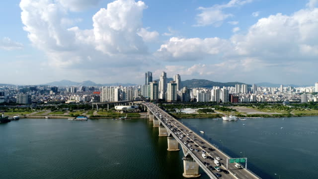 view of ttukseom park beside cheongdamdaegyo bridge and city buildings in jayang-dong, seoul at day - traffic time lapse stock videos & royalty-free footage