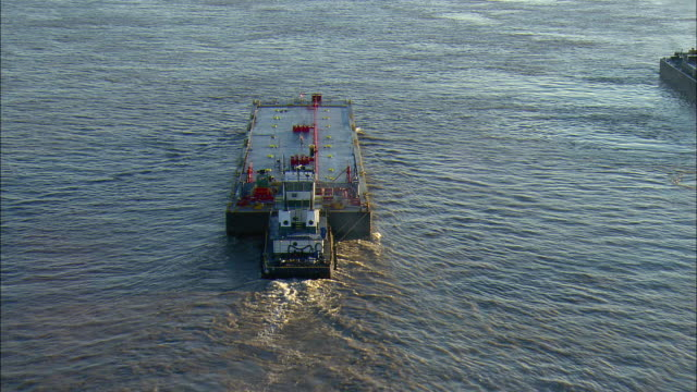 WS POV AERIAL View of tugboat pushing fuel barge on Mississippi River / New Orleans, Louisiana, USA