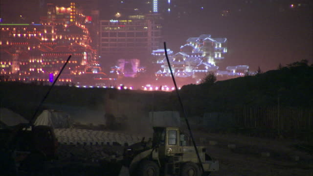 ws zo tu view of tunnel project and city at night / chongqing, sichuan province, china  - 建設機械点の映像素材/bロール