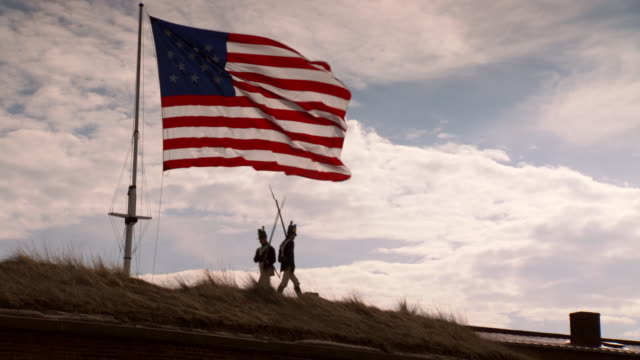 WS View of Two American soldiers trade places guarding Fort McHenry with the Star Spangled banner flapping in wind / Baltimore, Maryland, United States