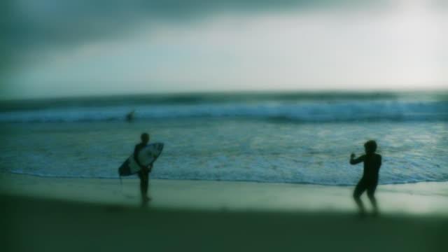 WS View of two boys on beach, one holding surfboard / Laguna Beach, California, USA