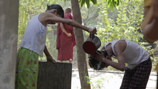 ws view of two boys rincing their hair with water / bagan, mandalay division, myanmar - pagan stock-videos und b-roll-filmmaterial