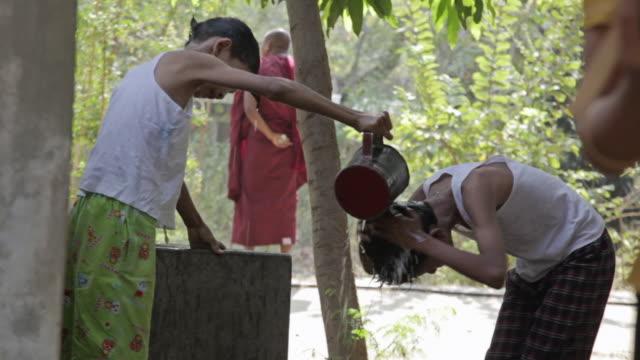 ws view of two boys rincing their hair with water / bagan, mandalay division, myanmar - bagan stock videos & royalty-free footage