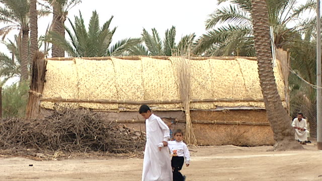 view of two boys walking in front of a mudhif in the marsh arab village of alchubayish mudhif architecture dates back to sumerian times - fries säulengebälk stock-videos und b-roll-filmmaterial