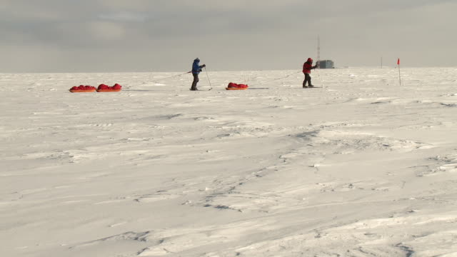 WS PAN View of two figures on skis pulling pack sleds across South Pole ice with orange marker flag and building / South Pole, Antarctica