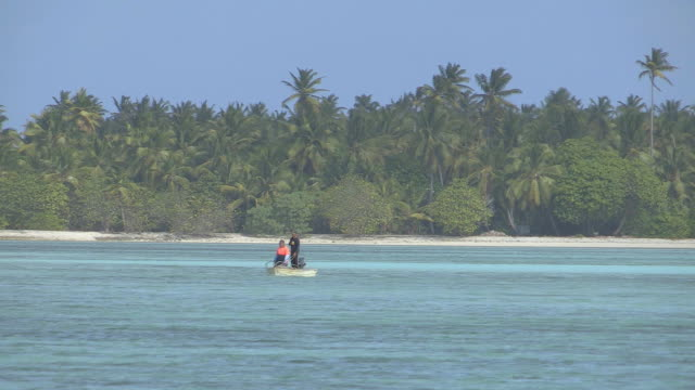 WS TS View of Two Fishermen in Small Boat off Exotic Island Coastline / Keeling, Shire of Cocos, Australia