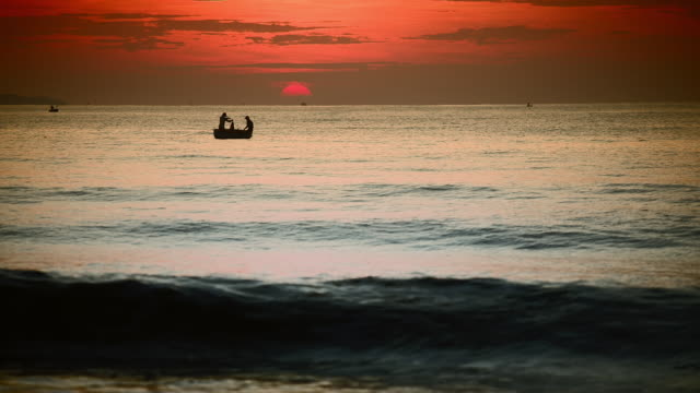 ws view of two fishermen work together in simple fishingboat floating on silvery sea and silhouetted by pink rising sun / mui ne, vietnam - religiöse darstellung stock-videos und b-roll-filmmaterial