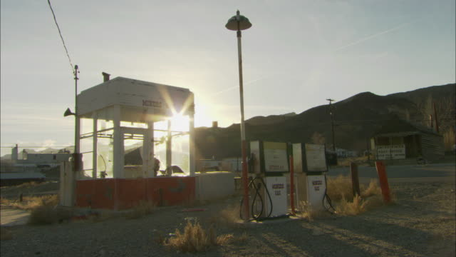ws view of two gas pumps and teller booth in small ghost town / silver peak, nevada, usa - ガソリンスタンド点の映像素材/bロール