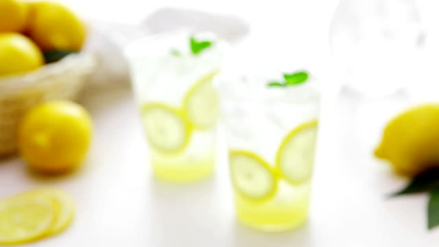 view of two glasses of lemonade with a basket of lemon - fizzy lemonade stock videos & royalty-free footage