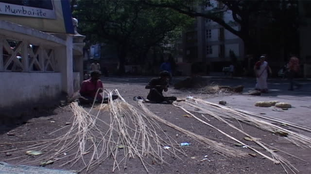 view of two indian men sitting on a street, weaving baskets. bulrush or rush weaving is an ancient craft in india. weavers use pliable grasses and... - reed grass family stock videos & royalty-free footage