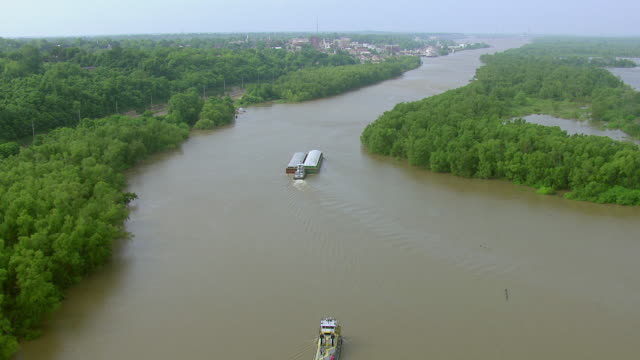 WS AERIAL View of two large barges traveling on Mississippi River with Vicksburg / Vicksburg, Mississippi, United States